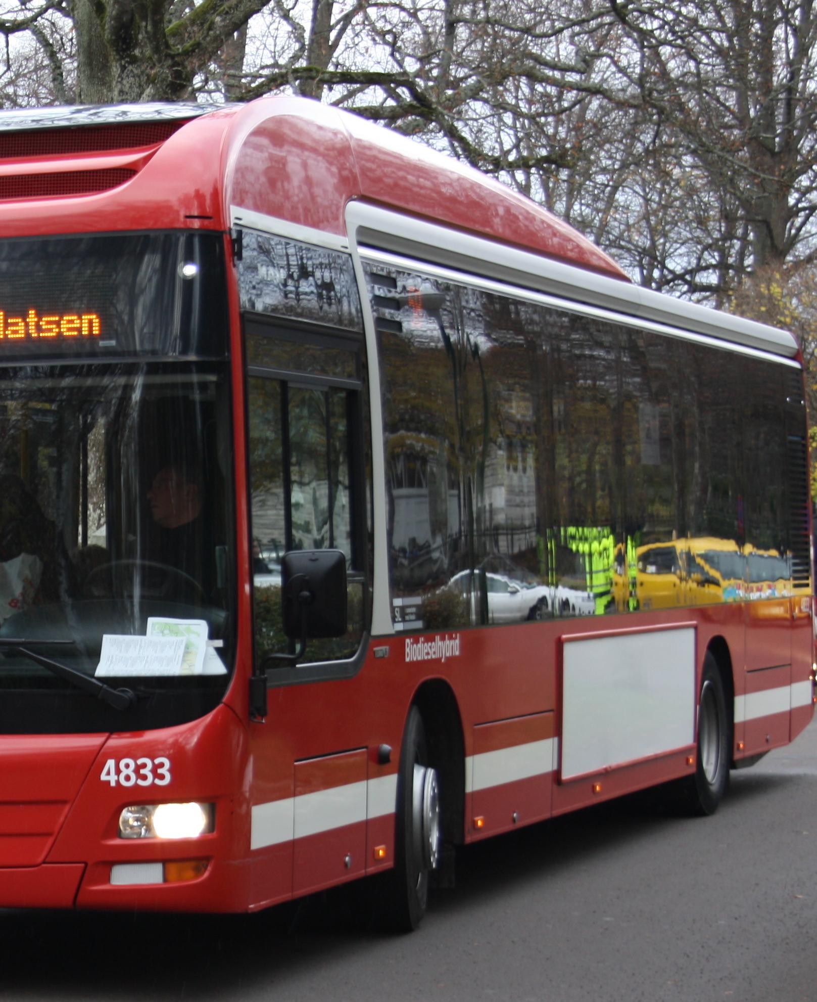 Syntolkning: Röd stadsbuss, i bussens fönster speglas bilar och hus.