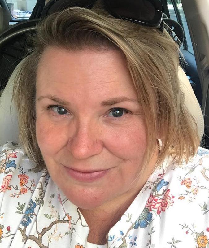 Maria, solbränd med solglasögon i pannan, iklädd ljus mönstrad topp, sitter i förarsäte i bil, i bakgrunden syns rullstolen baksätet.