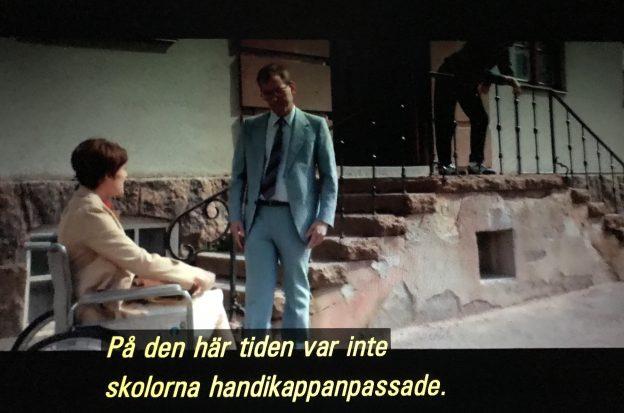 """Filmruta. Skolgård, trappa till huvudentrén, nedanför trappan sitter Sonja i rullstol, hon pratar med man som står. Speakerröst/textremsa """"På den tiden var inte skolorna handikappanpassade."""""""
