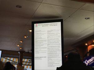 Foto av ljustavla med meny på, upphängd i taket på aktuell restaurang.